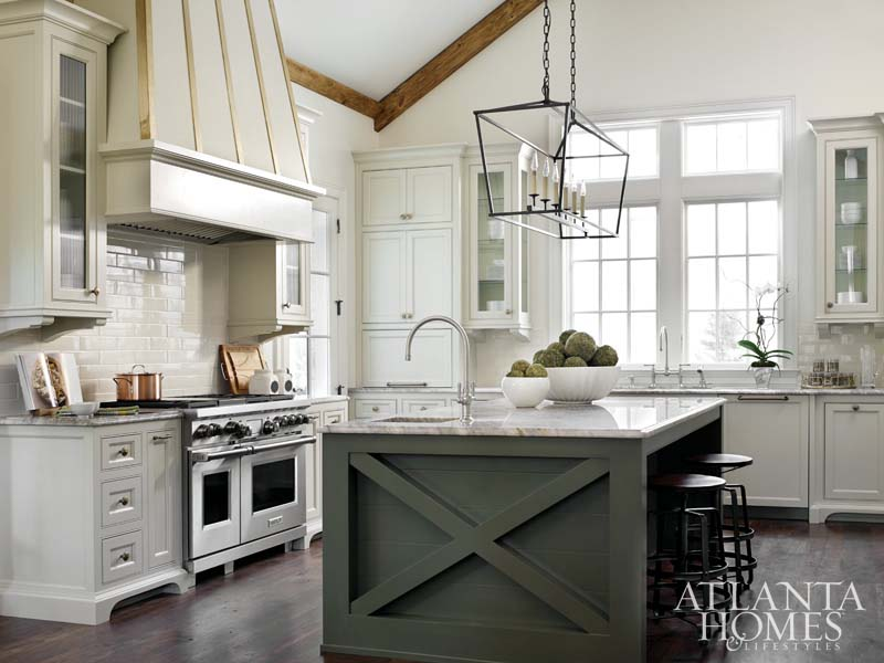 Gorgeous white kitchen with grey island, magnificent range hood, and professional range