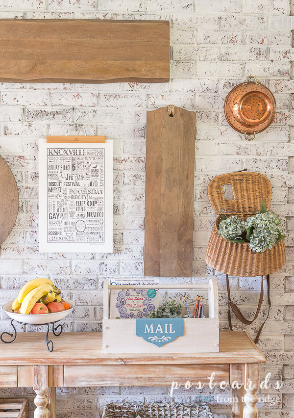 wooden toolbox organizer and wood cutting boards against painted brick wall