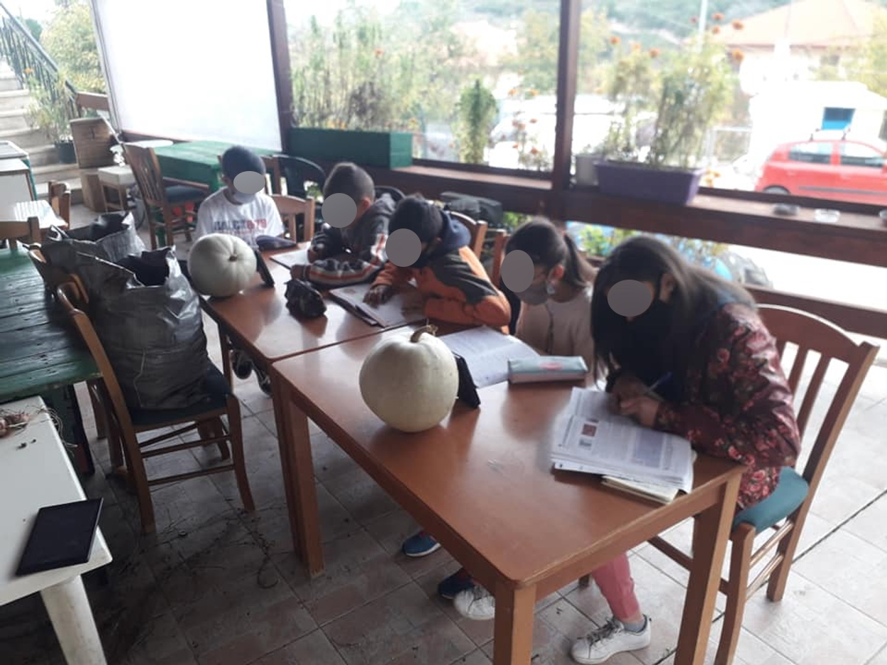 Τηλεκπαίδευση με μπουφάν και κινητό στην αυλή καφενείου