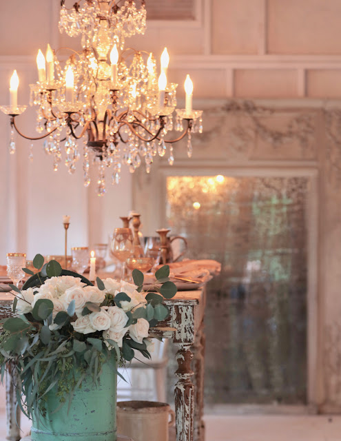 Vignette with flowers and chandelier in a barn