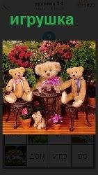 Около кустов на за столиком и на стульях сидят игрушки медведей разной величины
