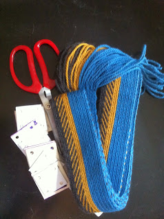 A photograph of a tablet woven band made using the pattern above, next to a red handled pair of scissors and a set of weaving tablets