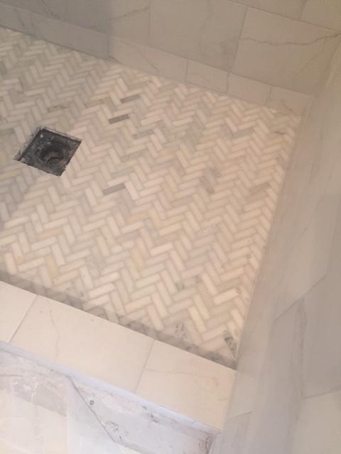 Herringbone carrera marble shower floor under construction - Hello Lovely Studio