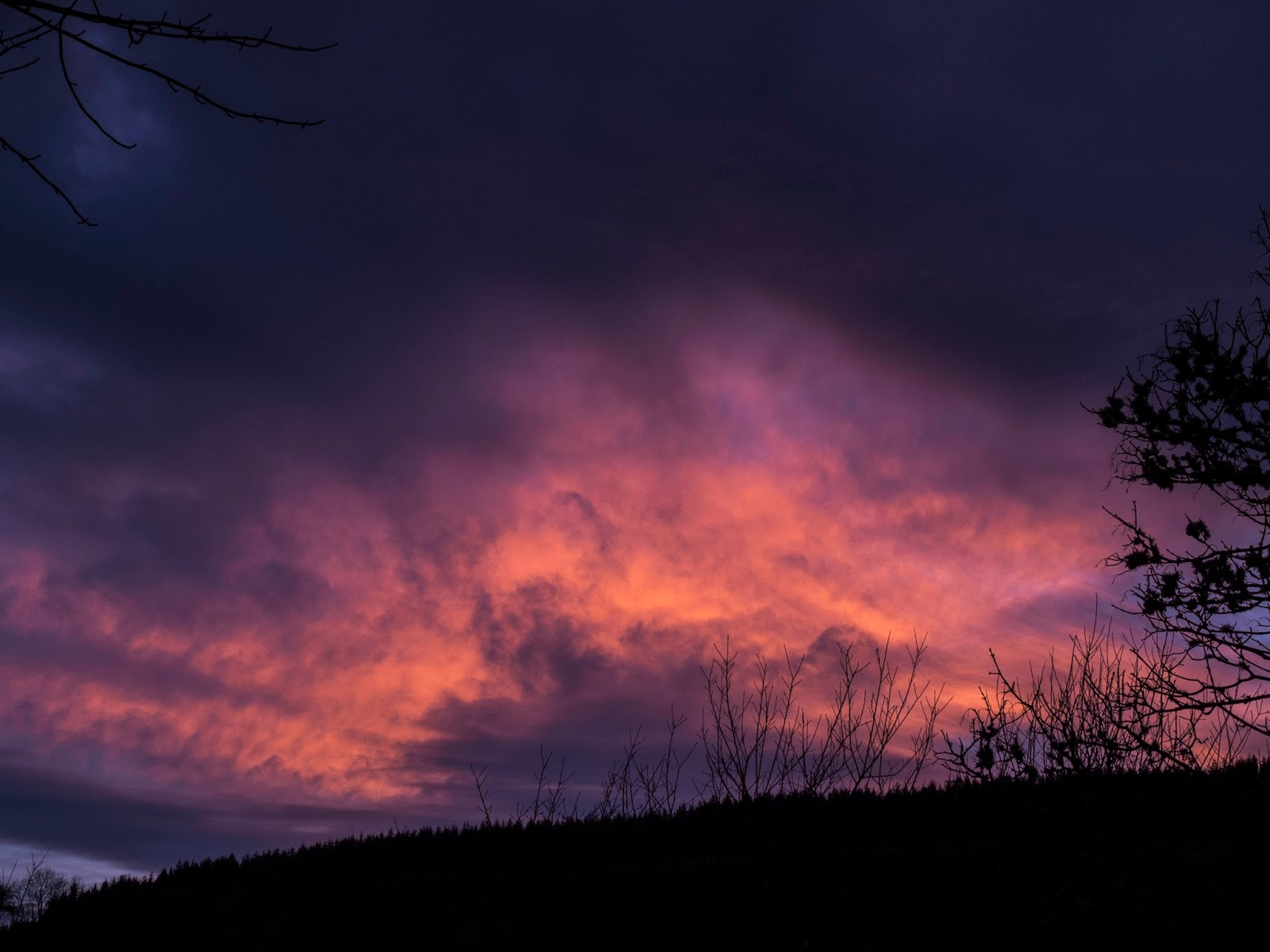 Dramatic navy to pink cloud display at sunset in the mountains in North Cork.
