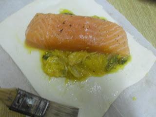 hojaldre con salmón sobre cama de mezcla de endivias y naranja cocinadas al azafrán