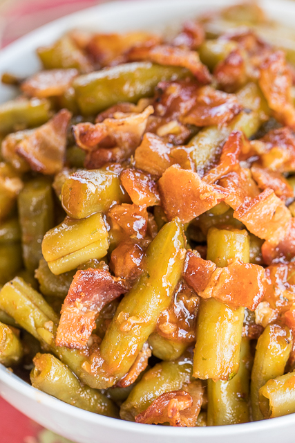 BBQ Smothered Green Beans - canned green beans baked in bacon, and a homemade BBQ sauce. This is the most requested green bean recipe in our house.Everybody gets seconds. SO good!! Great for a potluck. Everyone asks for the recipe! Super easy to make.