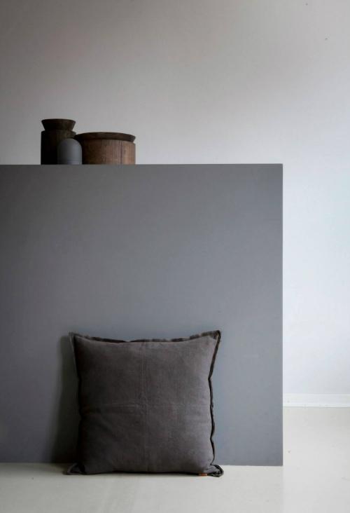 Leuchtend Grau: Vor einer grauen Wand lehnt ein graues Kissen