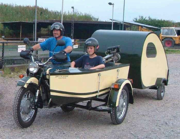 3-wheeled motor cycle with a boat sidecar towing a tiny trailer