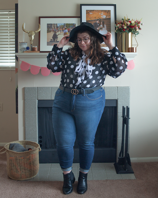 An outfit consisting of a wide brim black hat, a black and white blouse dotted blouse with a contrasting white on black dotted neck tie tied in a bow, tucked into high waist blue denim jeans and black chelsea boots.