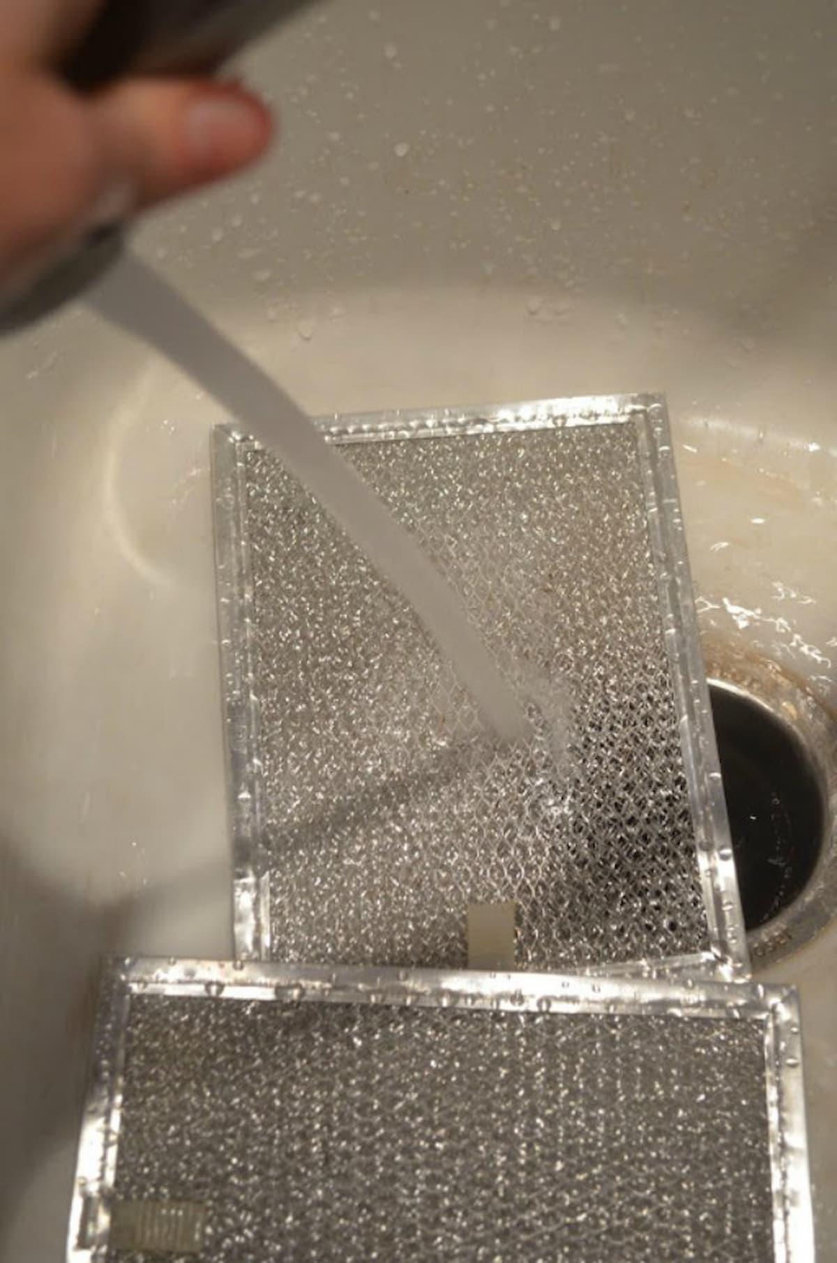 Clean Hood Vent Filter being rinsed under water.