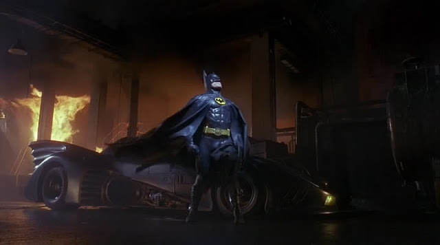 Batman strikes a pose as a building burns down behind him. Seven lives were lost that night.