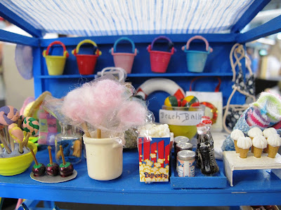 Details of the stock on a one-twelfth scale seaside stall, including toffee apples, candy floss, pop corn and ice creams.