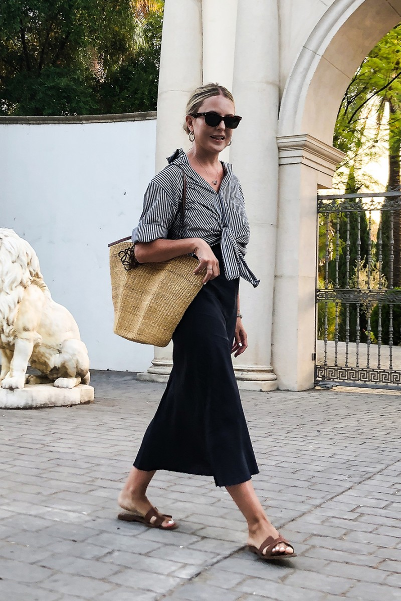 Easy Stylish Summer Outfit Idea —Trini Gonzalez in a striped button-down shirt, black slipdress, cat-eye sunglasses, and Hermes flat sandals