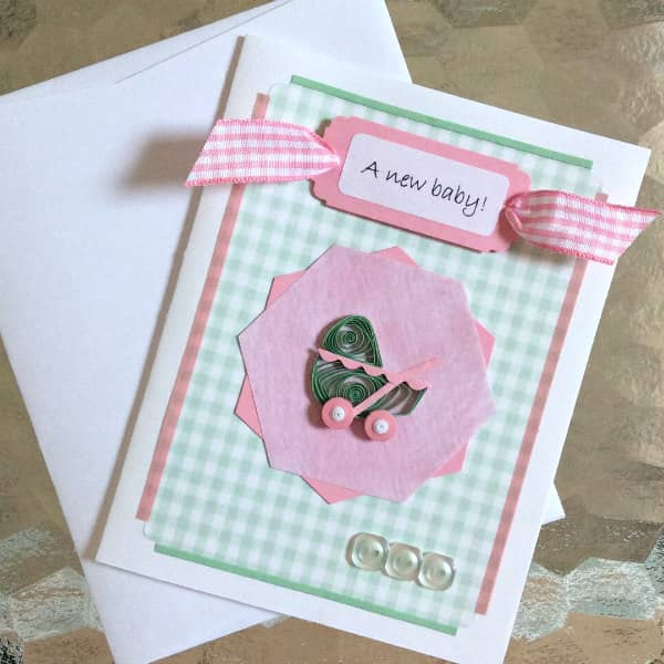 pink and green quilled baby carriage card and white envelope