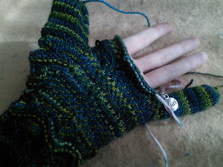 Someone wearing a partially finished dark green knit glove. The thumb and little finger are complete and the remaining fingers are not.  The remaning stitches are held on scrap yarn. At the base of the little finger a small stitch marker is clipped into the work.