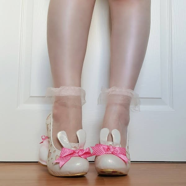front of legs wearing mesh socks and bunny eared shoes with pink bow on front