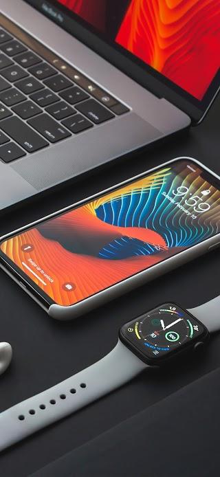 Space gray iPhone X beside Apple watch wallpaper