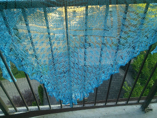 A lace, light-weight blue shawl hanging over a fence.  There are black circular beads in the edging.