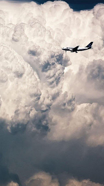 خلفية هاتف تصوير طائرة وسط سحب كثيفه