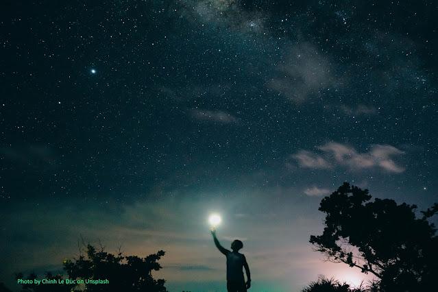 Silhueta de uma pessoa, a noite, simula tocar a Lua