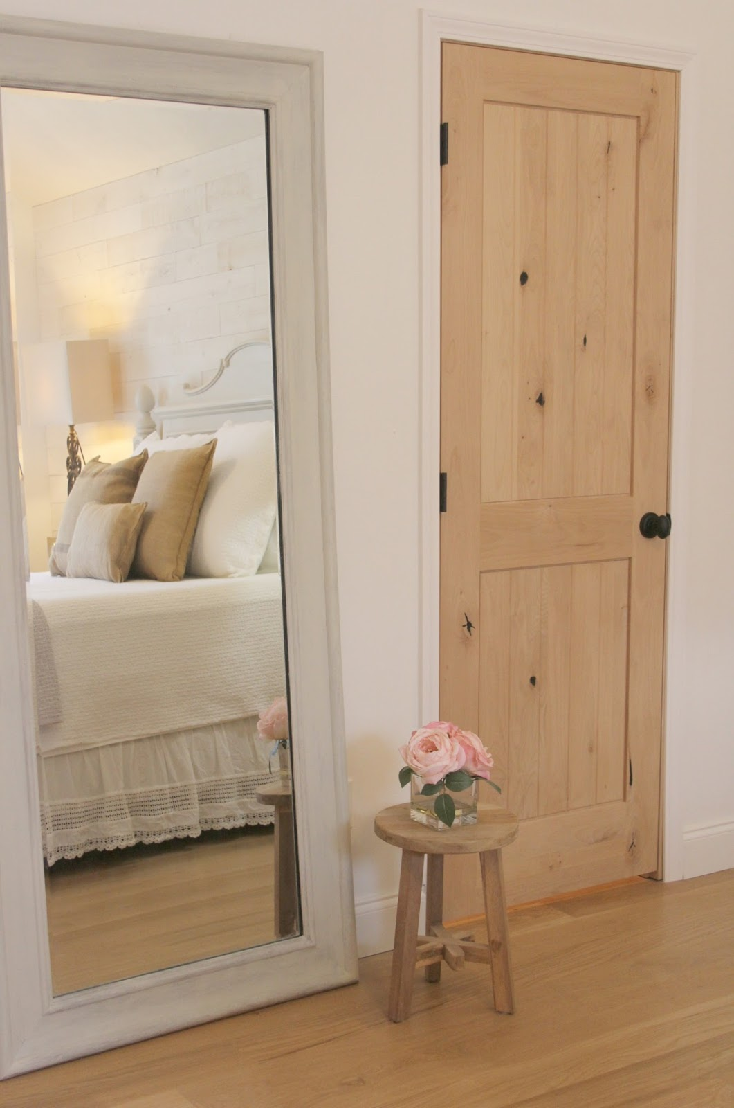 reflection of bed in mirror and knotty alder closet door in master bedroom of Hello Lovely Studio's fixer upper