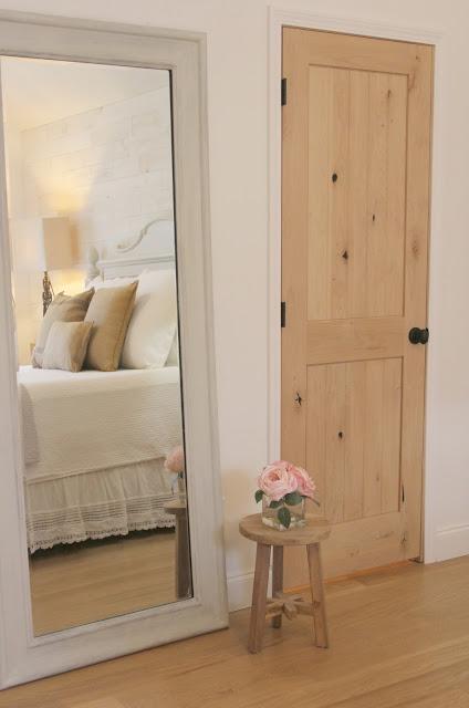 reflection of bed in mirror and knotty alder closet door in master bedroom of Hello Lovely Studio's fixer upper