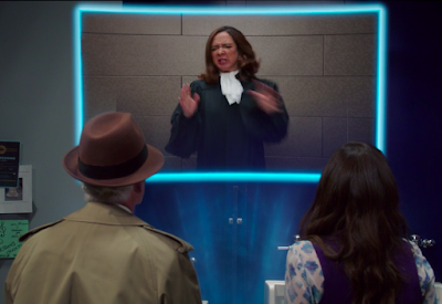 Michael and Janet are facing a floating screen where we see the Judge with a grimace on her face and blurred hands because her arms were moving wildly when I took the screenshot