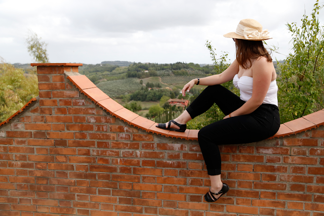 Katy Sitting on Wall Looking Out at View Over Tuscan Countryside Italy