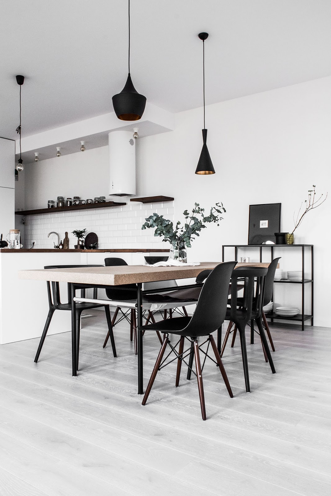 scandinavian apartment, black and white interior kitchen with eames chairs and tom dixon lights