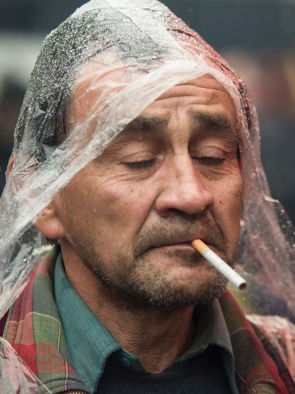 Primer plano de un hombre triste fumando bajo la lluvia