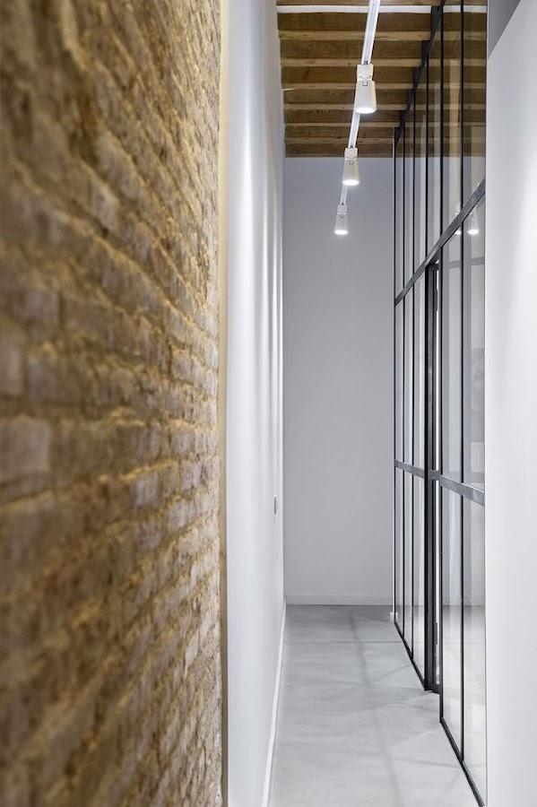 Muro vidrio y pared de piedra en pasillo
