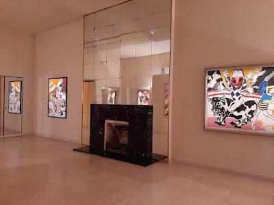 exposição de quadros em sala com lareira