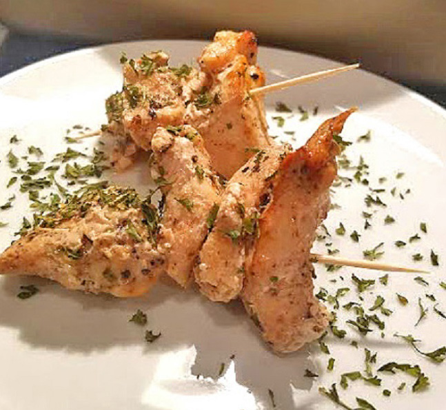 Baked chicken kabobs marinated, baked then skewered on a plate with dried parsley for a backyard picnic