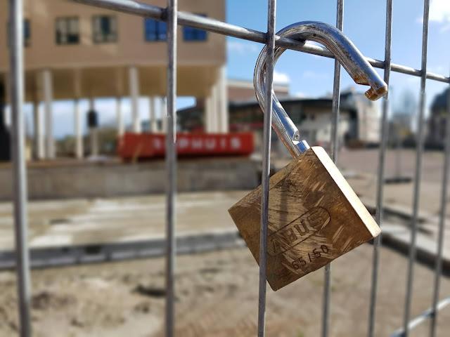 Aan een hek dat een bouwterrein bij de Leeuwenbrug afsluit hangt een open Abus-hangslot.