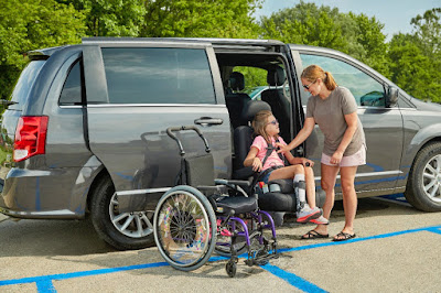 A grey minivan is parked in a disabled parking spot. A little girl is seated in a transfer seat, which is extended outside of the rear passenger door. Her mother reaches down to unbuckle her seatbelt. The girl's wheelchair is positioned right next to her.