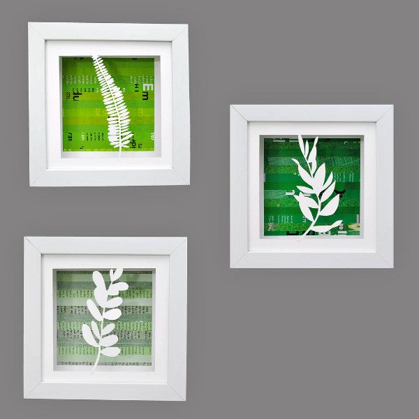 trio of framed art with white papercut foliage on rolled magazine page green backgrounds