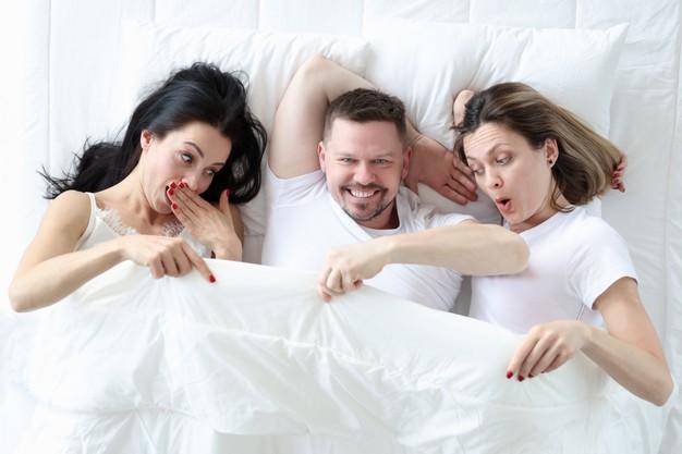 Un hombre y dos mujeres en la cama