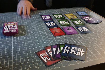 Foul Play Card Game table set up in play with hand reaching to take a card