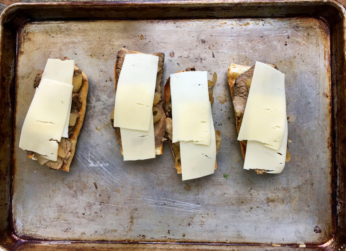 Cheese on meat on bread on a sheet pan.