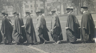 line of students at commencement, some wearing military uniforms
