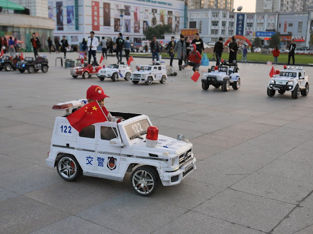 boy driving an electric kiddie car with a PRC flag in Mudanjiang, China