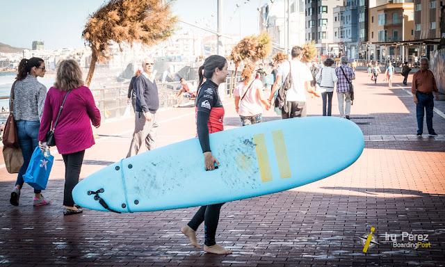 Chica con tabla de surf en la playa de Las Canteras