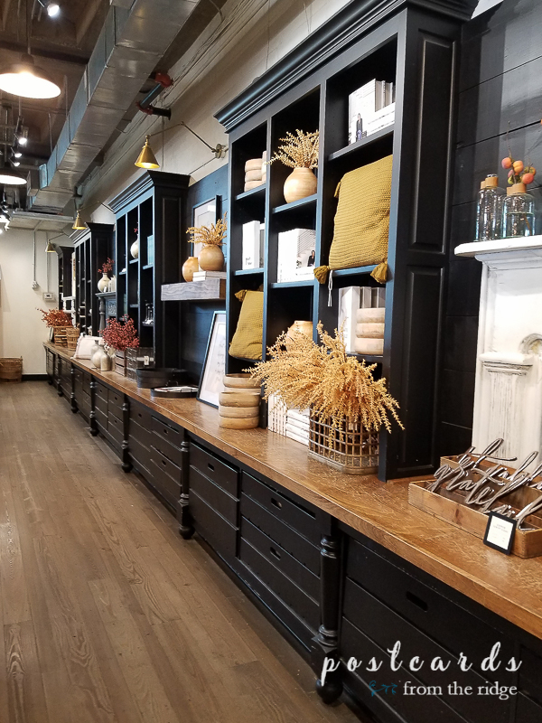 long wall of black shelving in Magnolia market store