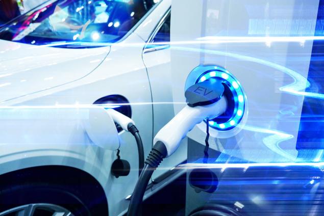 A imagem mostra um carro elétrico sendo abastecido, nesse caso, ele está carregando sua bateria na tomada própria para carros elétricos. O carro é branco e a imagem possui tons de azul.