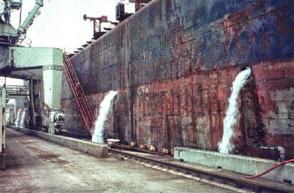 Ship releasing ballast into a port