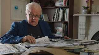 Jim Sheridan at a desk reading a newspaper