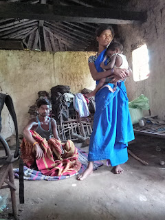 Jaisingh Baiga with his wife and daughter in their hut