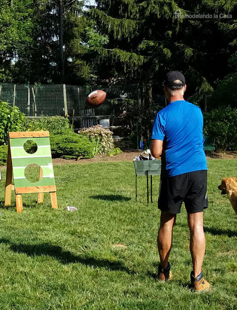backyard with a football toss and man throwing football at it with Labrador retriever dog by the side