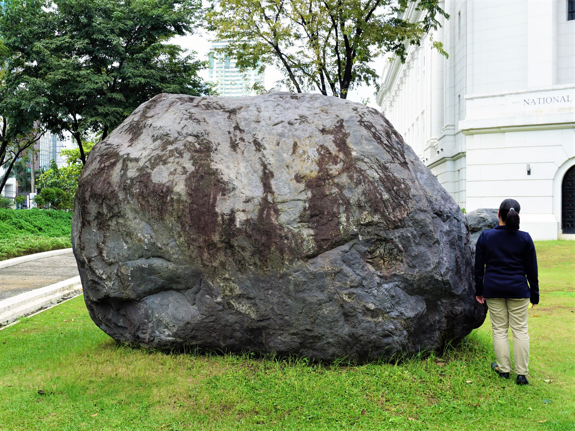 girl beside gigantic rock boulders are at the entrance of National Museum of Natural History Philippines
