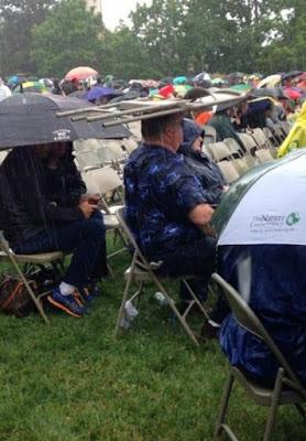 Lustige Menschen bei Regen - Stuhl als Regenschirm